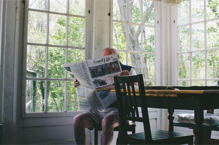 部屋で一人新聞を読む男性の写真