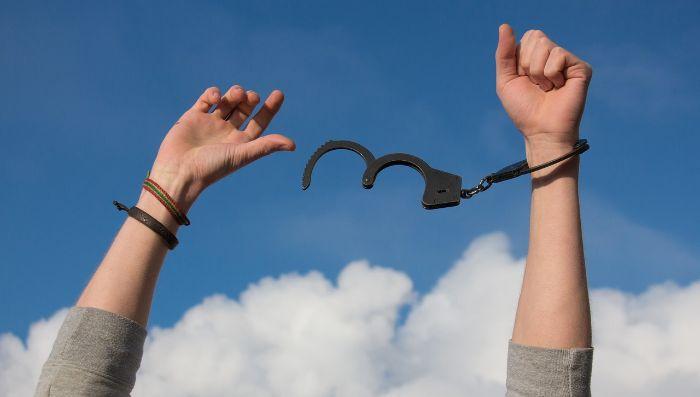 両手を青空に掲げて手錠を外している写真