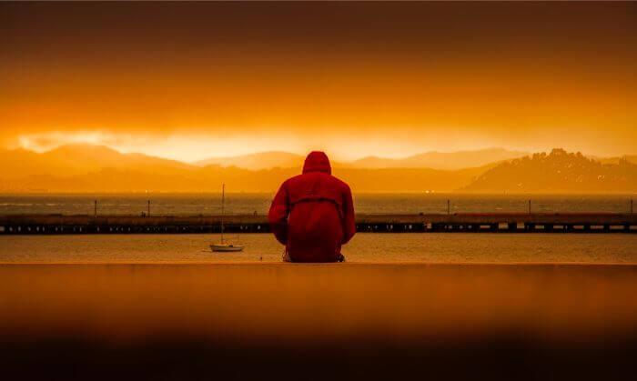 夕日の中海を見ている落ち込んだ男性の写真