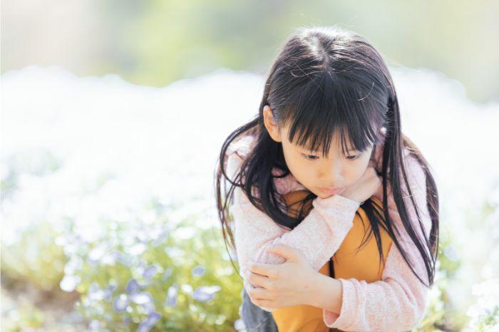 花畑でうつむく女の子の写真