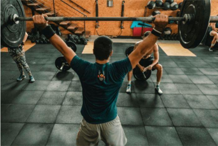 大きなダンベルを両腕で持つ上げる男性の写真