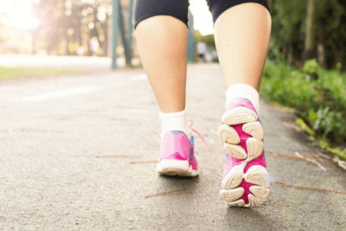 女性がスニーカーを履いて歩く写真