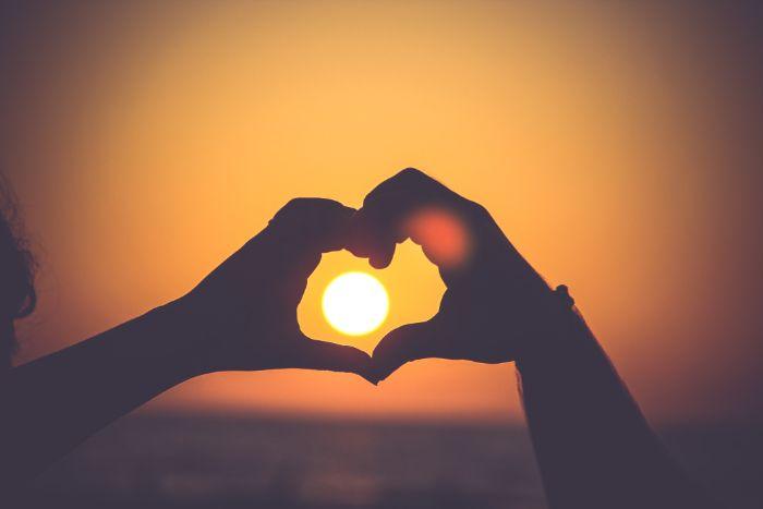 夕日をハートマークにした手で縁取っている写真