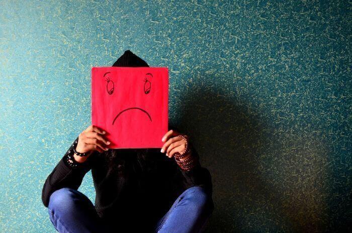 赤い紙に悲しい顔文字を書いて座っている男性写真